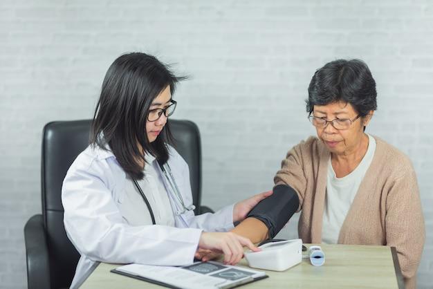 Médecin vérifiant la pression vieille femme sur fond gris Photo Premium
