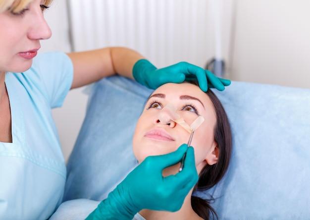 Médecin vérifiant le visage de la femme, le njse après chirurgie plastique, rhinoplastie, blépharoplastie. Photo Premium