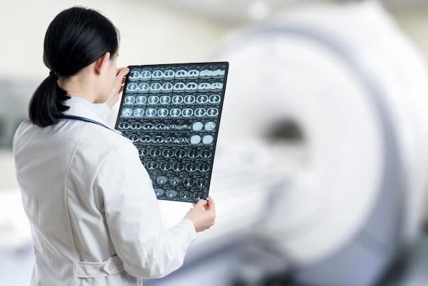 Un médecin vérifie la radiographie du cerveau par balayage au cerveau à l'hôpital de la chambre du patient. Photo Premium