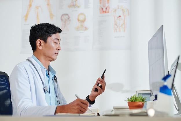 Médecin Vietnamien Mature Sérieux Vérifiant Les Messages Texte Des Patients Et Notant Ses Plaintes Photo Premium