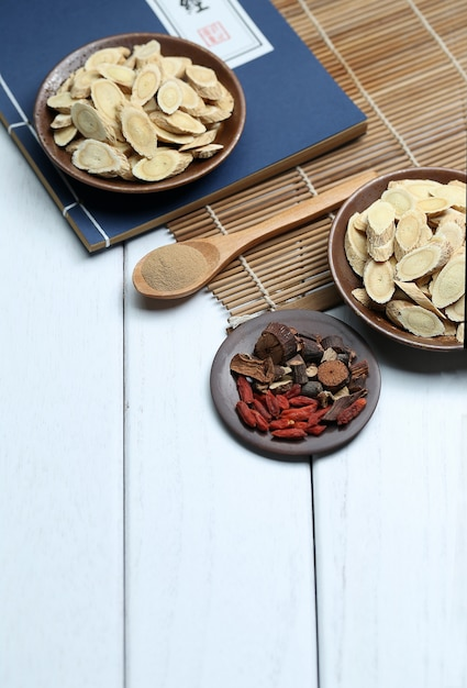 Médecine traditionnelle chinoise et ancien livre médical sur bureau blanc Photo gratuit