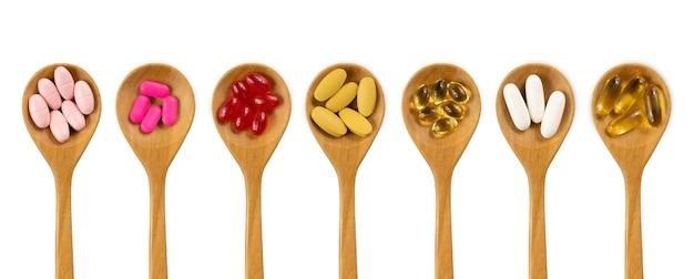 Médecine, Vitamine Et Supplément Dans Une Cuillère En Bois Isolé Sur Blanc Photo Premium