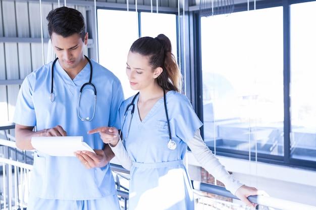 Médecins à l'aide de tablette numérique dans le couloir de l'hôpital Photo Premium