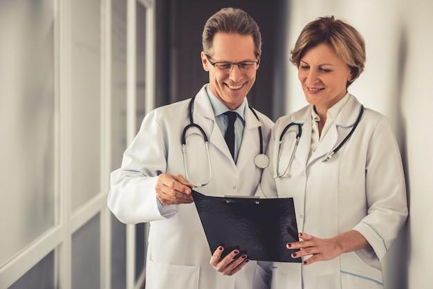 Des médecins en blouse blanche discutent de documents. Photo Premium