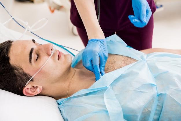 Les Médecins Donnent La Réanimation à Un Patient De Sexe Masculin Dans La Salle D'urgence. Massage Cardiaque Photo Premium