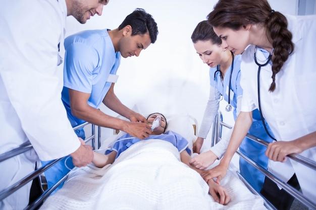 Médecins examinant un patient au lit à l'hôpital Photo Premium