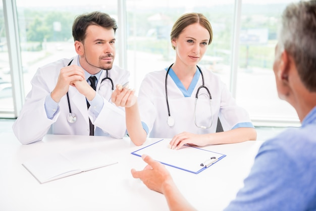 Médecins expliquant le diagnostic à un patient de sexe masculin mature. Photo Premium