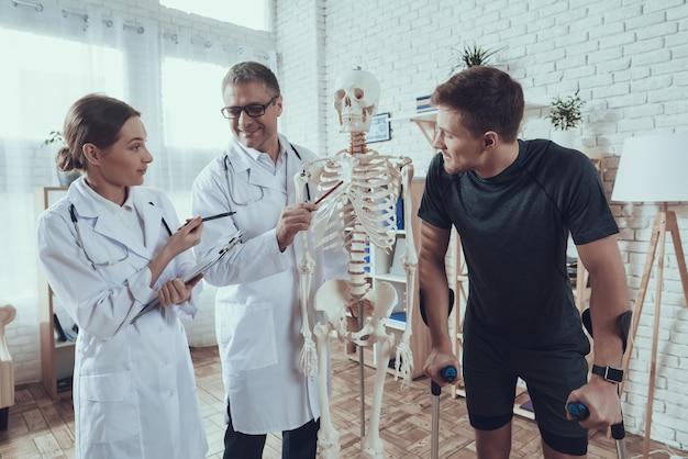 Les médecins montrent un squelette à un athlète blessé Photo Premium