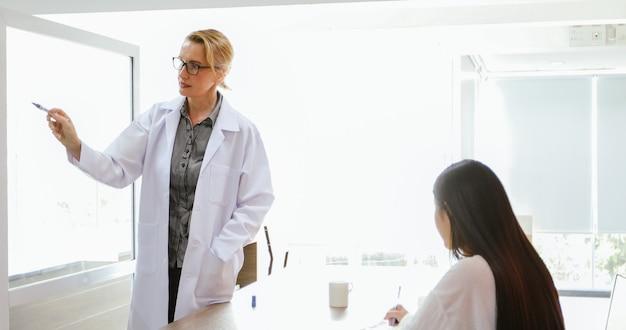 Des médecins ou des scientifiques enseignent et expliquent aux étudiants et aux patients qui écrivent à bord Photo Premium