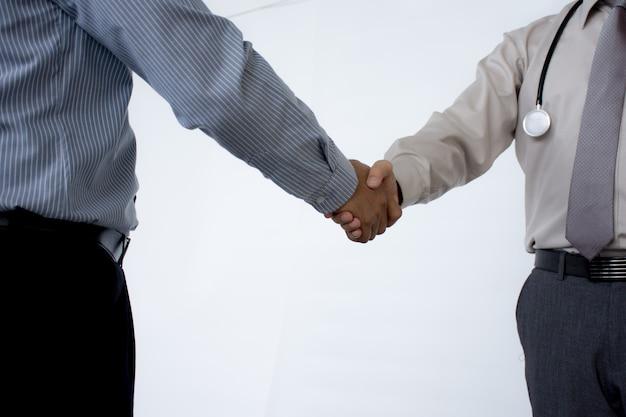 Médecins se serrant la main les uns aux autres en terminant la réunion médicale isolée sur fond gris. Photo Premium