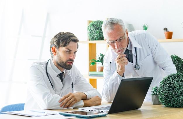 Médecins sérieux regardant un écran d'ordinateur portable Photo gratuit