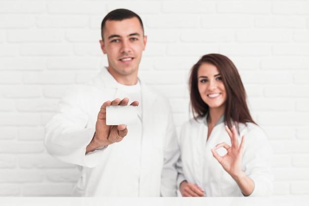 Médecins souriants montrant ok signe et carte mock up Photo gratuit