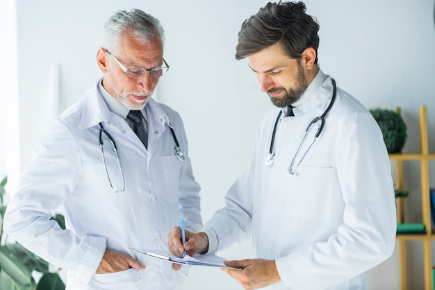 Médecins travaillant avec des papiers au bureau Photo gratuit