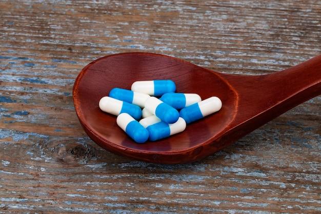 Médicaments, Comprimés Et Gélules Sur Cuillère En Bois. Photo Premium