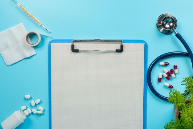 De médicaments, de fournitures médicales placées à côté de planches à écrire et d'outils à médecin sur fond bleu. Photo gratuit