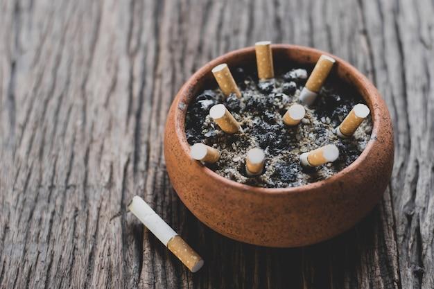 Le mégot de cigarette dans le pot est placé sur un vieux plancher en bois, concept de la journée mondiale sans tabac. Photo Premium