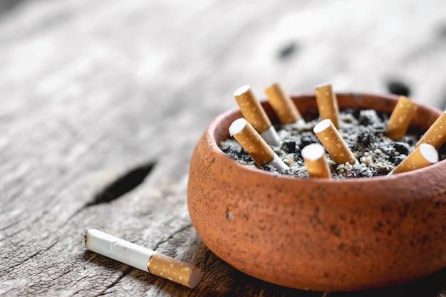 Le mégot de la cigarette est placé sur un vieux plancher de bois. Photo Premium