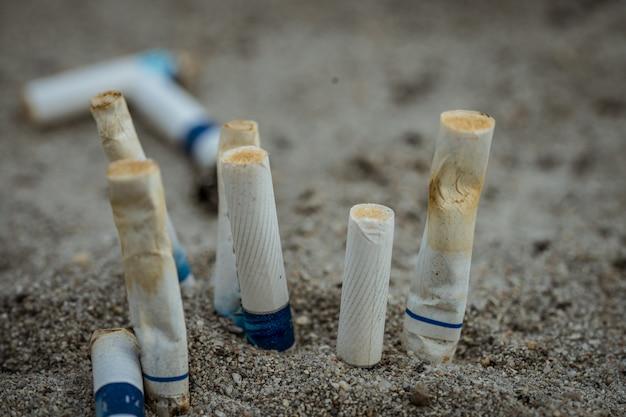 Mégots de cigarettes après utilisation, puis laissés sur le sable Photo Premium