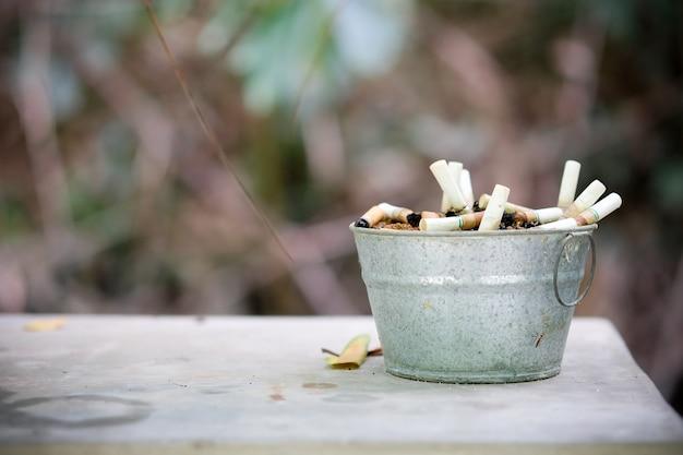 Les mégots de cigarettes sont nombreux dans le cendrier en zinc Photo Premium