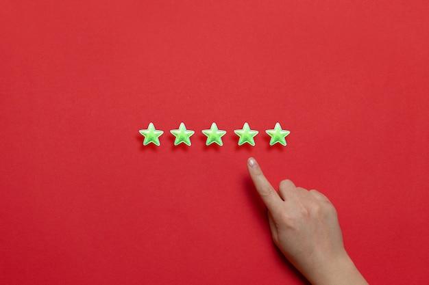 La meilleure évaluation de la prestation de services. étoiles jaunes vives et une main féminine avec un index sur un fond rouge Photo Premium