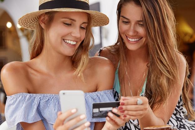 Meilleures Amies Les Femmes Se Réunissent à La Cafétéria, Heureuses De Faire Des Achats En Ligne Avec Un Téléphone Intelligent Et Une Carte En Plastique Photo gratuit