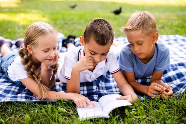 Meilleurs amis lisant sur une couverture de pique-nique Photo gratuit