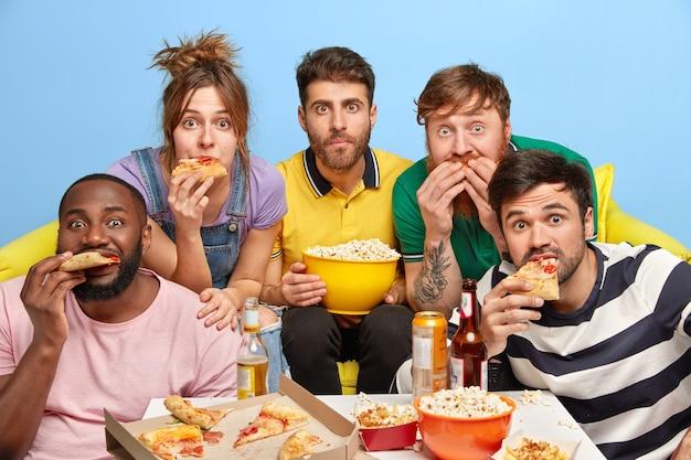 Les Meilleurs Amis Regardent La Télévision à La Maison, Profitent De Leur Journée De Congé, Mangent De Savoureuses Pizzas Et Du Maïs Soufflé Photo gratuit