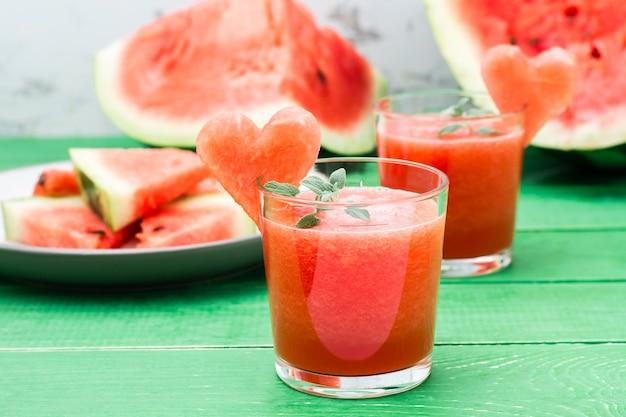 Mélange De Boisson Fraîche Avec Des Feuilles De Menthe Et Un Cœur De Melon D'eau Dans Des Verres Sur Une Table En Bois Photo Premium