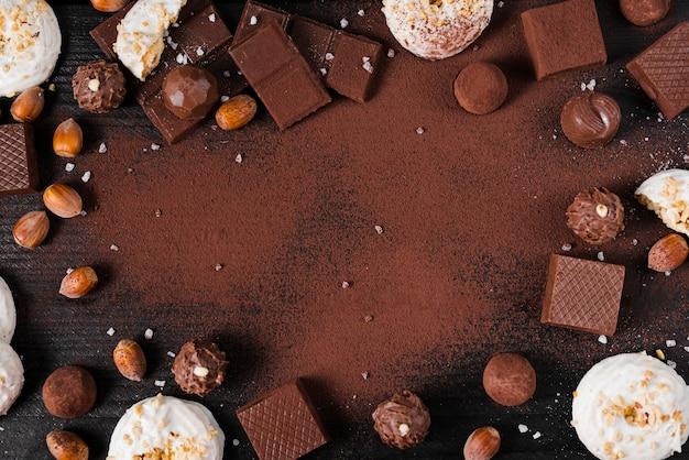 Mélange de bonbons au chocolat plat et poudre de cacao sur fond rose avec espace de copie Photo gratuit