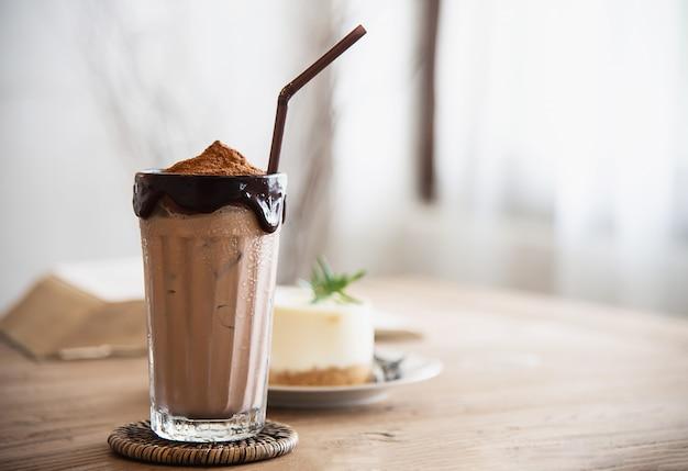 Mélange de cacao et de cacao avec un gâteau dans un café Photo gratuit