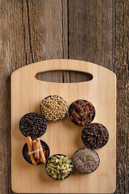 Mélange coloré de différentes épices sur une planche de bois Photo Premium