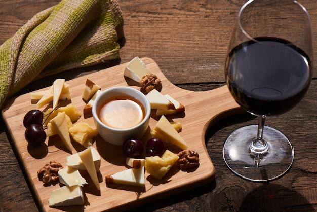 Mélange De Fromage De Parmesan, Mozzarella, Camembert Sur Une Planche De Bois Et Un Verre De Vin Rouge Photo Premium
