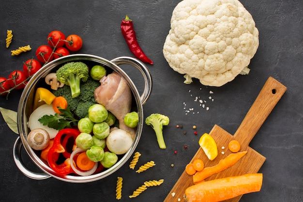 Mélange de légumes et de pilon de poulet dans un plat avec des carottes sur une planche à découper et du chou-fleur Photo gratuit
