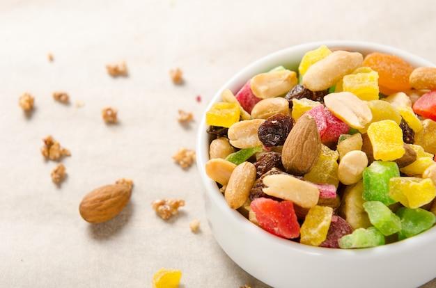 Mélange de noix et de fruits secs - amandes, cacahuètes, raisins secs sur fond blanc dans un bol. Photo Premium