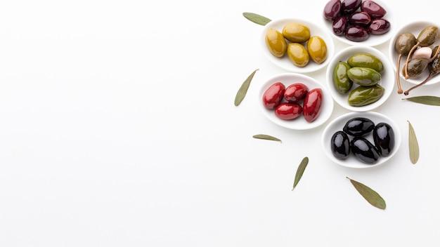 Mélange d'olives noir rouge vert violet jaune et d'huile avec espace de copie Photo gratuit