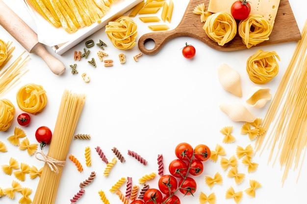 Mélange de pâtes plates non cuites avec tomates et fromage à pâte dure Photo gratuit