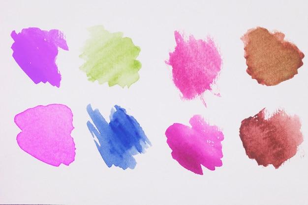 Mélange de peintures marron, verte, bleue, violette et rose sur papier blanc Photo gratuit