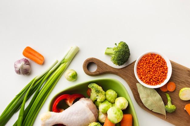 Mélange Plat De Légumes Sur Une Planche à Découper Et Dans Un Bol Avec Une Baguette De Poulet Et Une Cuillère Photo gratuit