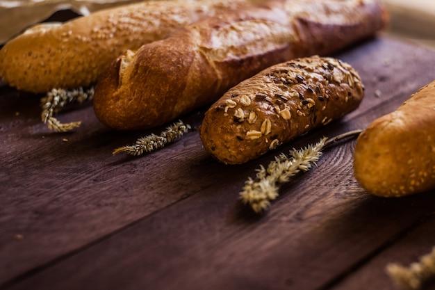 Mélange de sortes de baguettes sur une table en bois. produits de boulangerie. Photo Premium