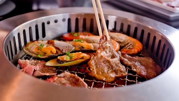 Mélange de viande rôtie et de fruits de mer et de baguettes sur le barbecue grill sur le rôti. Photo Premium
