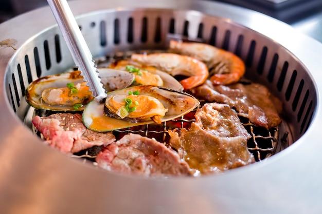 Mélange de viande rôtie et de fruits de mer sur le barbecue grill sur le rôti. Photo Premium