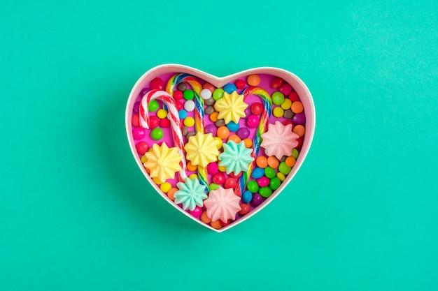 Mélanger Les Bonbons Au Chocolat Se Trouvent En Forme De Boîte Cadeau De Coeur Sur Fond Coloré Photo Premium