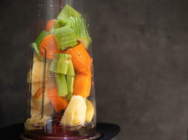 Mélangeur avec des légumes frais. tranches de céleri, de pomme et de carotte dans un bol mélangeur pour un smoothie. Photo Premium