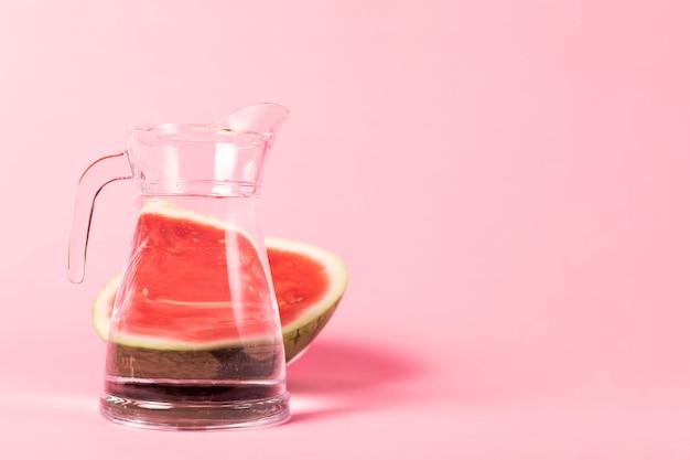 Melon d'eau demi-tranché avec un pichet d'eau Photo gratuit