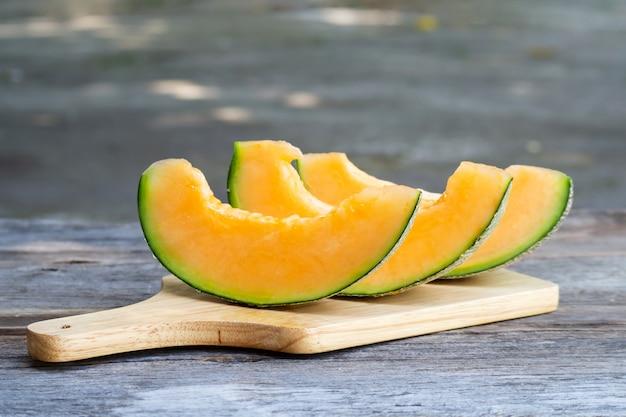 Melon frais en tranches sur une planche de bois. fruit sucré Photo Premium
