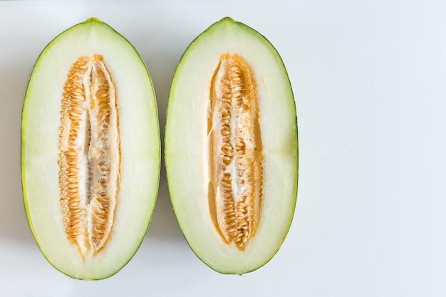 Melon de miellat fraîchement coupé sur fond blanc Photo gratuit