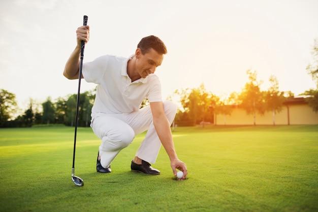 Un membre du club de golf joue sur un parcours au coucher du soleil. Photo Premium