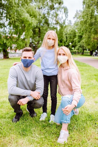 Les Membres De La Famille S'embrassent, Souriant à La Caméra Avec Des Masques En Tissu. Photo Premium