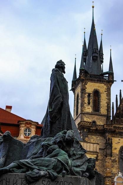 Memorial Jan Hus A Regardé La Tour De L'église De Týn Par Derrière Par Temps Nuageux à Prague. Photo Premium