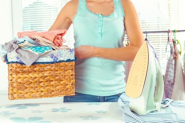 Ménagère apportant une énorme pile de linge sur la planche à repasser Photo Premium